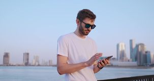 De man draait het aantal op de telefoon en spreekt op de achtergrond van het panorama van Doubai Handclose-up stock video