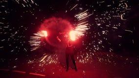 De man draait in zijn handen een bal van brand De grote brand toont stock video