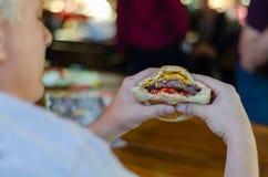 De man eet hamburger met genoegen royalty-vrije stock afbeeldingen