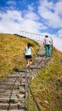 De man en de vrouw beklimmen aan de bergtop in de zonnige dag Royalty-vrije Stock Afbeelding
