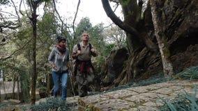 De man en de vrouw beklimmen de steen opvoeren de berg stock footage