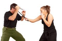 De man en de vrouw bestrijden het gebruiken van mes en knuppel Royalty-vrije Stock Foto's