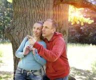 De man en de vrouw dichtbij een eik in de zomerdag tonen aan de kant stock fotografie