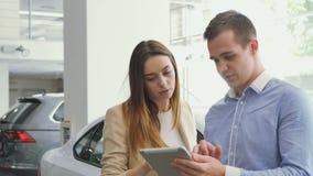 De man en de vrouw kijken op de tablet in het autohandel drijven stock footage