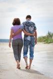 De man en de vrouw lopen op het strand Stock Fotografie