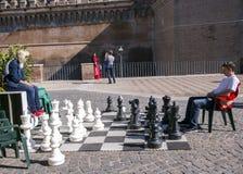 De man en de vrouw spelen een schaak dichtbij een castel Sant'Angelo Royalty-vrije Stock Fotografie
