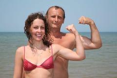 De man en de vrouw tonen bicepses stock foto