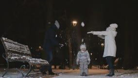 De man en de vrouw werpen op de sneeuw op weinig dochter in het park in slowmotion stock videobeelden