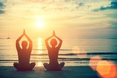 De man en de vrouwen het praktizeren van het silhouettenpaar yoga bij zonsondergang stock afbeeldingen