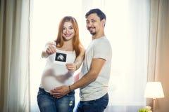 De man en een zwangere jonge vrouw wachten op een kind thuis B Royalty-vrije Stock Foto