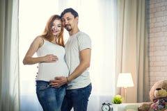 De man en een zwangere jonge vrouw wachten op een kind thuis B Stock Foto's