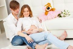De man en een zwangere vrouw zitten op de vloer royalty-vrije stock fotografie