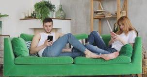 De man en de vrouw doorbladeren mobiele telefoons thuis zittend op de groene laag stock videobeelden