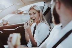 De man en de Vrouw eten Burgers in Tesla-Auto stock fotografie