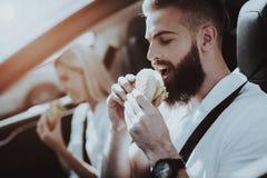 De man en de Vrouw eten Burgers in Tesla-Auto stock afbeeldingen