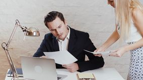 De man en de vrouw herzien documenten in het bureau