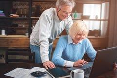 De man en de vrouw kijken aan het laptop ` s scherm en het lachen T royalty-vrije stock foto's