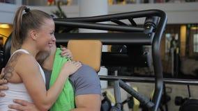 De man en de vrouw koesteren en kussen terwijl het zitten in gymnastiek stock video