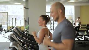De man en de vrouw lopen op tredmolen in sportclub Jong aangestoten paar stock video