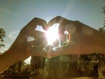 De man en de vrouw maken een hart rond de zon met hun handen Het mannetje en het wijfje dienen de stralen in en de glans van de z stock afbeelding