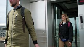 De man en de vrouw met bagage gaan in openlucht van lift uit stock footage