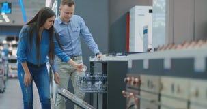 De man en de vrouw om de deur van afwasmachinetoestellen in de opslag te openen en met andere modellen vergelijkbaar te zijn om t stock videobeelden