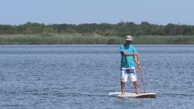 De man en de vrouw staan op paddleboarding stock footage