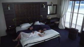 De man en de vrouw vallen gelijktijdig op bed in hotel van verschillende kanten stock videobeelden