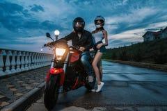 De man en de vrouw van het fietserpaar op een motorfiets van de zwarte en rode kleurensport Royalty-vrije Stock Afbeelding
