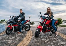 De man en de vrouw van het fietserpaar op een motorfiets van de zwarte en rode kleurensport Stock Afbeelding