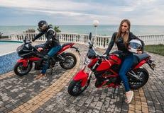 De man en de vrouw van het fietserpaar op een motorfiets van de zwarte en rode kleurensport Stock Afbeeldingen