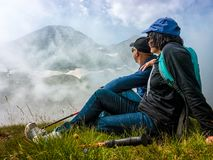 De man en de vrouw zitten op een helling en bewonderen de bovenkanten van bergen in de wolken royalty-vrije stock foto