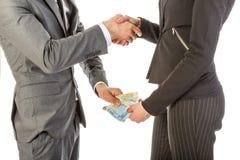De man geeft vrouwengeld terwijl het schudden van handen Stock Foto's
