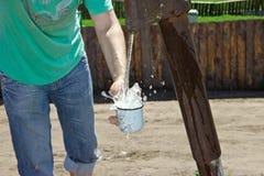 De man giet een Kop van water van de kolom (kraan) Royalty-vrije Stock Afbeelding