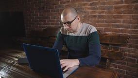 De man in glazen die enthousiast aan laptop werken Een mannelijke schrijver typt tekst op laptop toetsenbord stock videobeelden