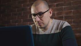 De man in glazen die enthousiast aan laptop werken Een mannelijke schrijver typt tekst op laptop toetsenbord, close-up stock video