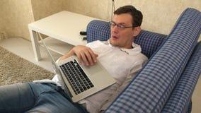 De man in glazen viel in slaap terwijl het werken in laptop aan zijn bank in zijn stadsflat stock video