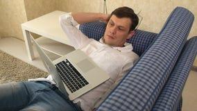 De man in glazen viel in slaap terwijl het werken in laptop aan zijn laag en ontwaakte abrupt in zijn stadsflat stock video