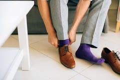 De man in grijze verslapping en purple kleden sokken bruine schoenen met royalty-vrije stock afbeelding