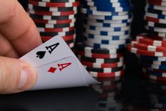 De man hand controleert de kaarten het spelen in het casino, opent twee azen, tegen de achtergrond van een grote weddenschap stock fotografie