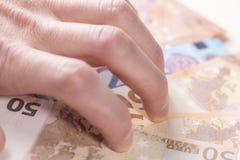 De man hand, met hebzucht wordt verdraaid, harkt een bos van Euro bankbiljetten dat aan zich stock foto's