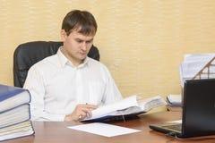 De man in het bureau aan meningsdocumenten royalty-vrije stock afbeelding
