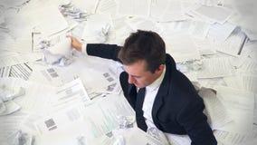 De man in het bureau die in document verdrinken