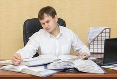 De man in het bureau die documenten in omslagen bekijken stock afbeeldingen