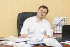 De man in het bureau die gelukkig glimlachen stock afbeeldingen