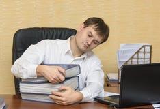 De man in het bureau gaat door omslagen met documenten Stock Afbeeldingen