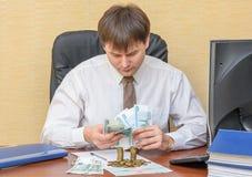 De man in het bureau, zei het geld liggend op het bevelschrift van uitvoering stock afbeelding