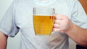 De man houdt een glas bier in hand Stock Afbeelding