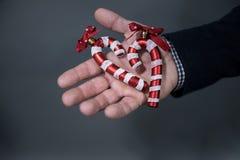 De man houdt een Kerstmisstuk speelgoed suikergoedriet stock afbeelding