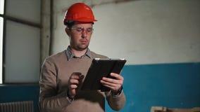 De man houdt een tablet in zijn hand, op het hoofd van een bouwer een beschermende helm stock video